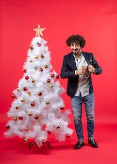 Nieuwjaarsviering met jonge man met een glas wijn dicht bij zijn hart in de buurt van versierde witte kerstboom