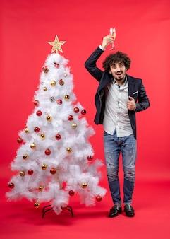 Nieuwjaarsviering met jonge man met een glas wijn op zijn hoofd in de buurt van versierde witte kerstboom