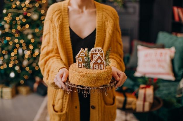Nieuwjaarsvrouw in een feestelijk interieur met slingers van kerstbomen en geschenken