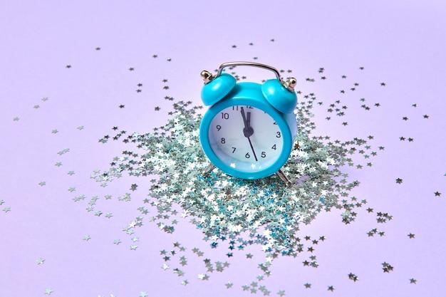 Nieuwjaarswekker met bijna twaalf uur op een lavendelachtergrond met vakantie helder zilveren kleine sterren klatergoud, kopieer ruimte.