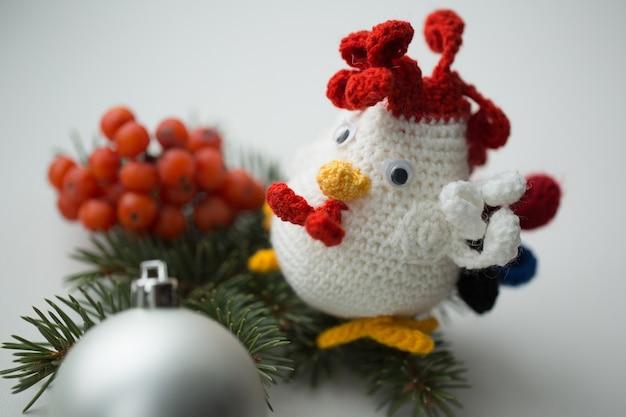 Nieuwjaarsymbool - handgemaakte haan met dennentakken en cranberry