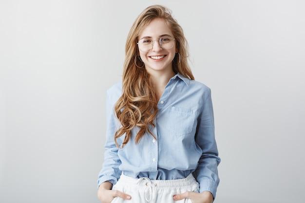 Nieuwkomer leert teamgenoten kennen. tevreden knappe zakenvrouw in transparante bril in blauw-kraag overhemd, breed glimlachend, verzekert van goede kwaliteit van het product over grijze muur