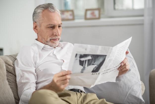 Nieuws lezen. geconcentreerde mannelijke persoon zittend op de bank en rimpelend voorhoofd terwijl u vooruit kijkt