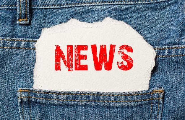 Nieuws op wit papier in de zak van blauwe denimjeans