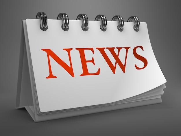 Nieuws - rode tekst op witte bureaubladkalender geïsoleerd op grijze achtergrond.