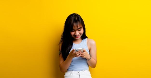 Nieuwsberichten en online communicatie foto van een mooie aziatische vrouw, schattig vrolijk pratend op mobiele telefoon geïsoleerd op gele muurachtergrond