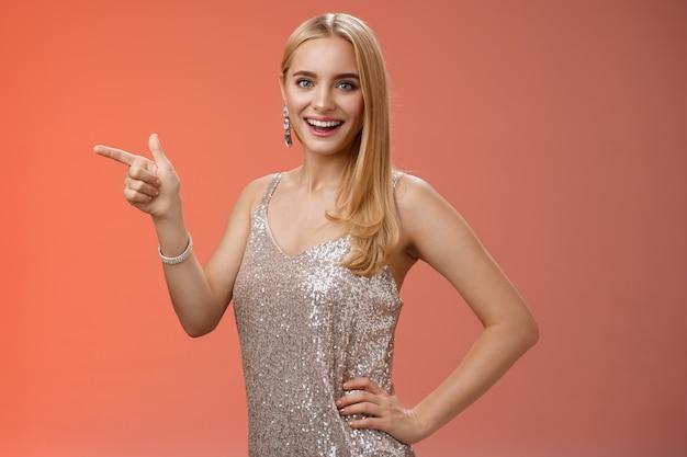 Nieuwsgierig aantrekkelijk kaukasisch blond jong 25s meisje in zilver glanzende luxe jurk greep hand taille zelfverzekerd wijzend links kijk camera geamuseerd vreugdevolle vermaakt feestmuziek concert, rode achtergrond.