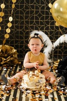 Nieuwsgierig baby meisje porren vinger in haar eerste verjaardagstaart smash.