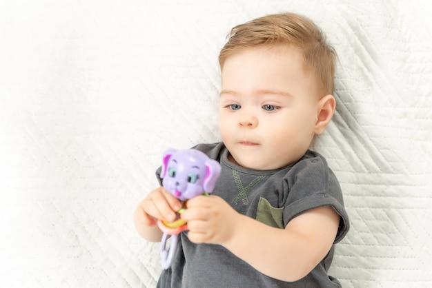 Nieuwsgierig babykind met rammelaar speelgoed liggend op bed in een zonnige slaapkamer.