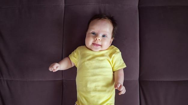 Nieuwsgierig babymeisje dat gele bodysuit met grappige foto draagt, ligt op de rug en lacht op een grote bruine bank in een ruime appartementkamerclose-up