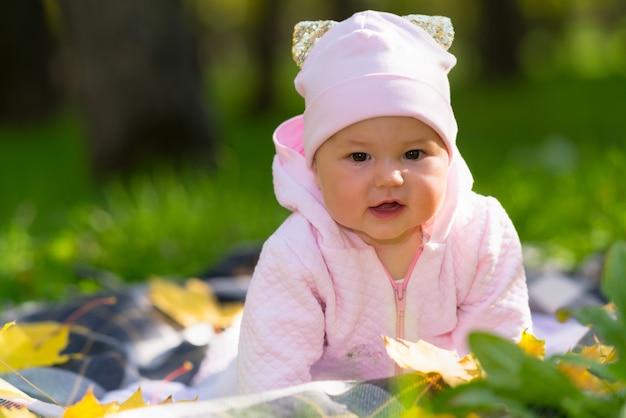 Nieuwsgierig babymeisje kijken naar de camera die zichzelf op haar armen opheft terwijl ze over een deken op het koper in een herfstpark kruipt