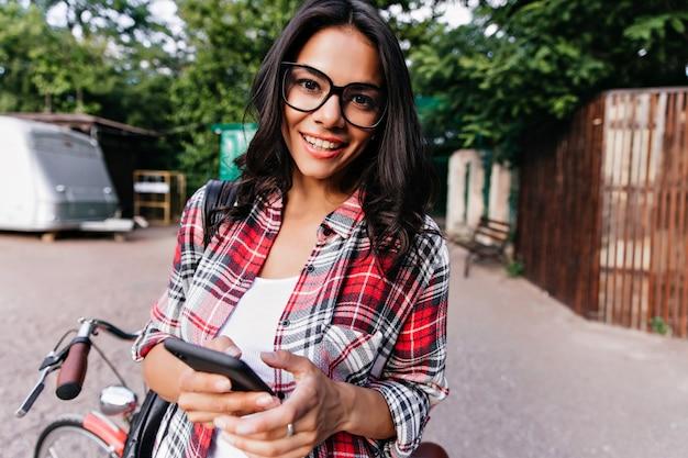 Nieuwsgierig brunette meisje met telefoon in de hand kijken. buitenfoto van prachtige latijnse dame die naast de fiets staat.