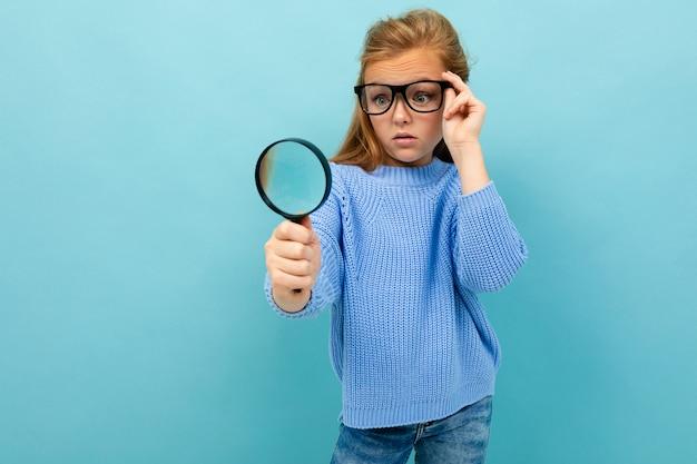 Nieuwsgierig europees meisje in glazen kijkt door een vergrootglas op lichtblauw