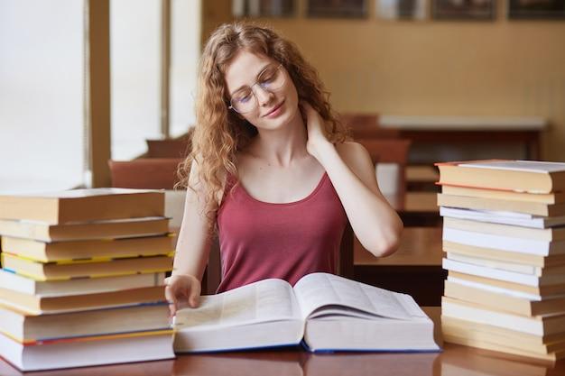 Nieuwsgierig goed opgeleide zitten aan de balie in de bibliotheek, examen voorbereiden, haar nek aanraken met één hand
