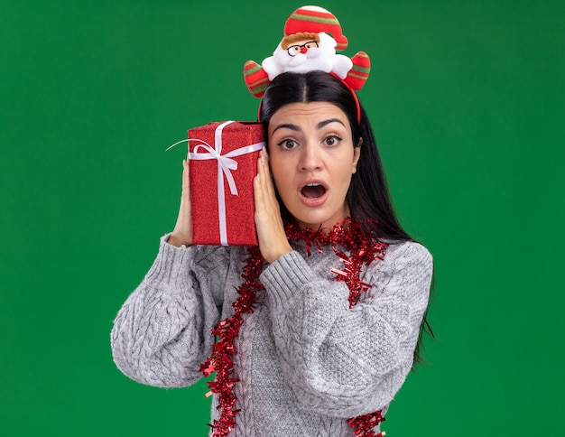 Nieuwsgierig jong kaukasisch meisje dragen hoofdband van de kerstman en klatergoud slinger rond nek houden geschenkpakket aanraken hoofd ermee kijken camera geïsoleerd op groene achtergrond