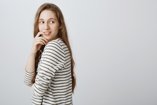Nieuwsgierig jong meisje dat erachter met verleidelijke glimlach kijkt