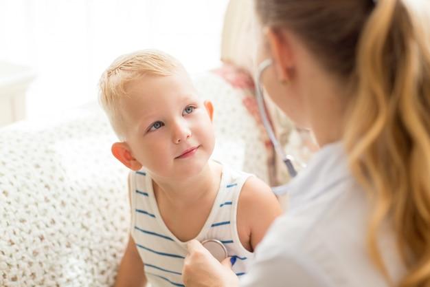 Nieuwsgierig kleine jongen die vrouwelijke arts bekijkt
