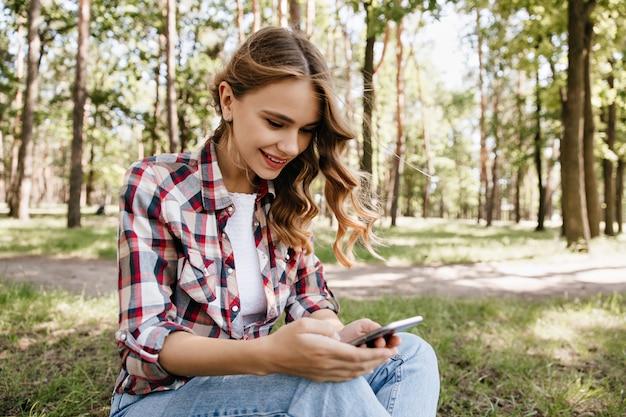 Nieuwsgierig krullend meisje sms-bericht zittend op het gras. buitenfoto van prachtige stijlvolle dame chillen in bos.