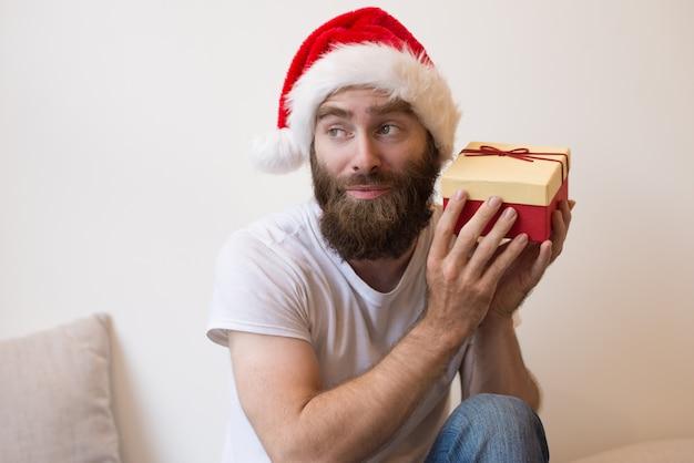 Nieuwsgierig man probeert te raden wat is in de doos van de gift van kerstmis