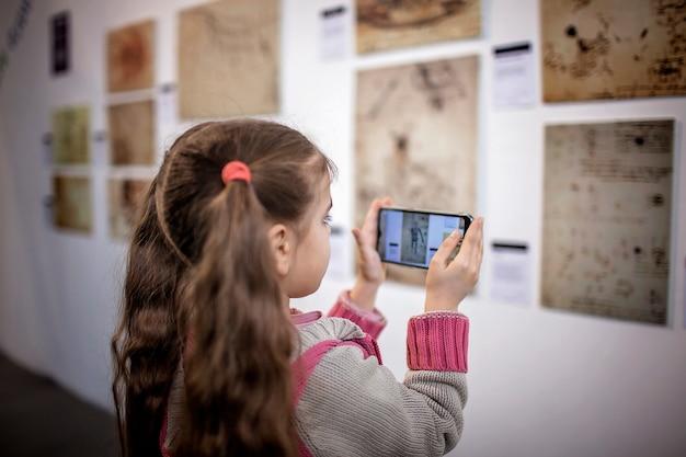 Nieuwsgierig meisje dat een tentoonstelling van hedendaagse kunst onderzoekt met een mobiele applicatie met augmented reality