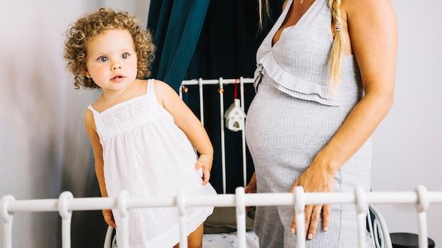Nieuwsgierig meisje dichtbij zwangere moeder