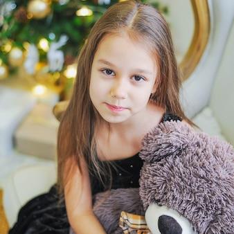 Nieuwsgierig meisje die terwijl het openen van kerstmis voorstelt glimlachen.