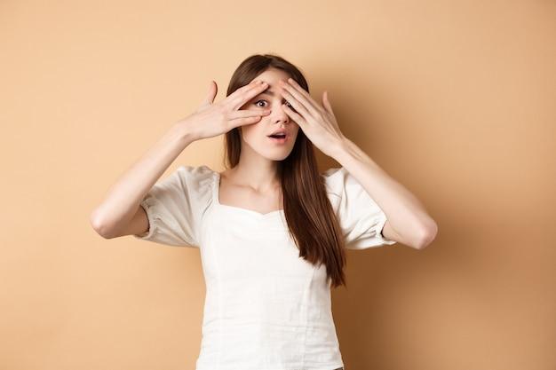 Nieuwsgierig meisje gluurt door haar vingers naar iets interessants, kan niet wachten om verrassing te zien, geïntrigeerd naar camera kijken, beige achtergrond.