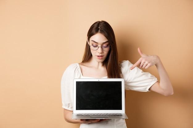 Nieuwsgierig meisje in glazen wijzend op laptopscherm, online deal bekijken, project demonstreren op computer, staande op beige achtergrond.
