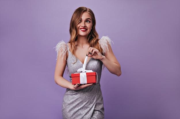 Nieuwsgierig meisje in zilveren feestelijke outfit die geschenkdoos opent op geïsoleerde muur
