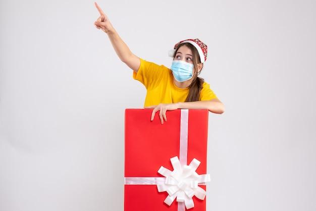 Nieuwsgierig meisje met kerstmuts wijzend op iets achter grote kerstcadeau op wit