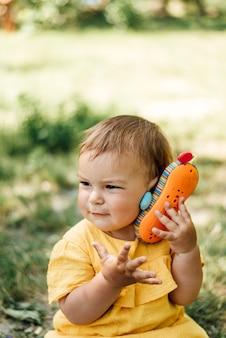 Nieuwsgierig meisje met speelgoed telefoon buitenshuis in zomerdag