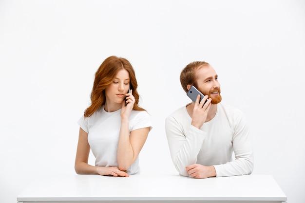 Nieuwsgierig meisje met vriend praten over de telefoon