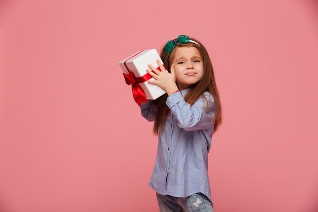 Nieuwsgierig meisje schudt de huidige geschenkverpakte doos dicht bij het oor en probeert te bepalen wat erin zit