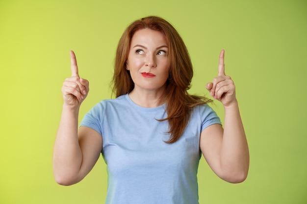 Nieuwsgierig nadenkend schattig roodharige vrouw van middelbare leeftijd gember moeder grijnzend denken opzij kijken wijsvingers beslissen keuze nadenken kiezen tussen varianten groene muur