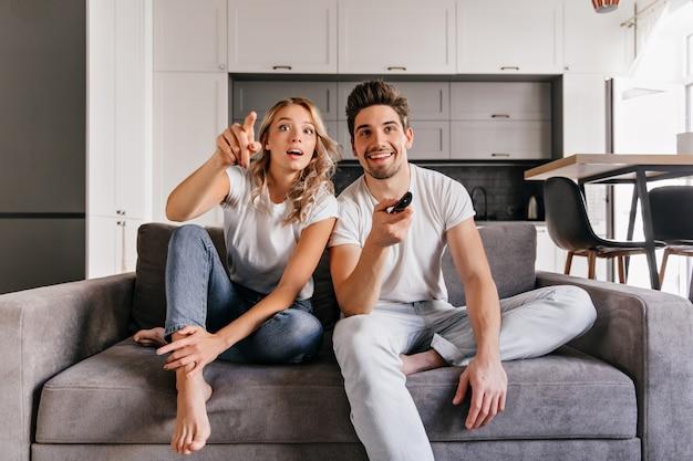 Nieuwsgierig paar zittend op een grijze bank. indoor portret van man en vrouw tv kijken.