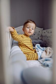 Nieuwsgierig schattig blond jongetje met mooie blauwe ogen, zittend in zijn wieg