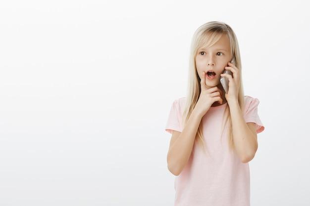 Nieuwsgierig slim blond meisje in roze t-shirt, praat op smarpthone en houdt vinger op lip, kaak laat vallen terwijl ze met interesse naar spreker luistert