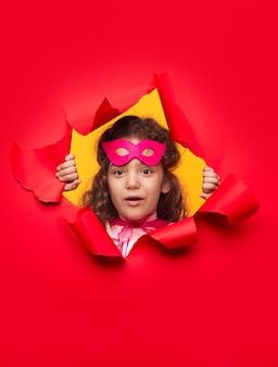 Nieuwsgierig superheld meisje kijkt door gat in papier