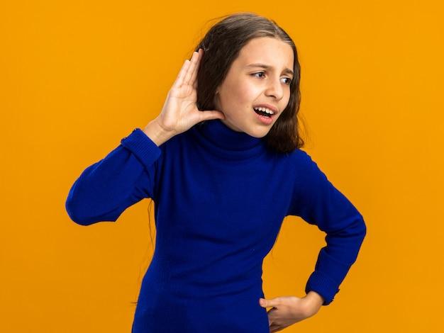 Nieuwsgierig tienermeisje dat naar de zijkant kijkt en de taille aanraakt, ik hoor je gebaar niet geïsoleerd op een oranje muur