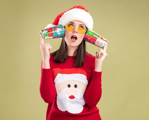 Nieuwsgierig vrij kaukasisch meisje dat de trui van de kerstman en hoed met glazen draagt die plastic kerstmiskoppen naast oren houdt die aan gesprekken luisteren