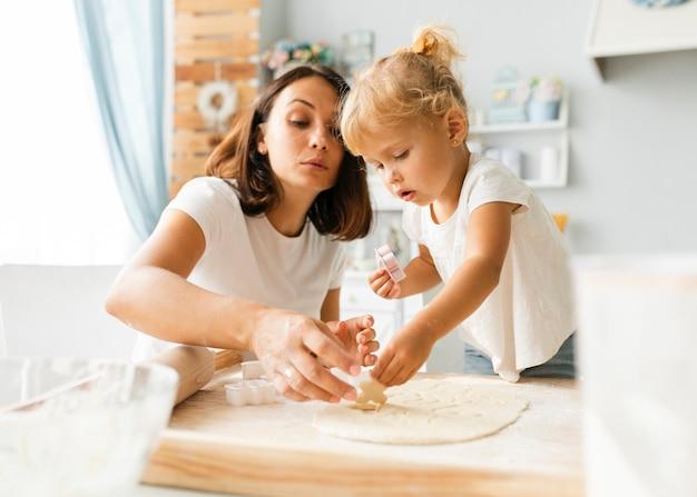Nieuwsgierig weinig dochter en moeder die koekjes voorbereiden