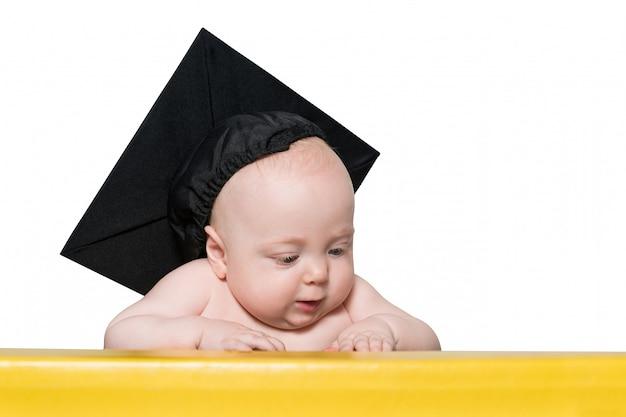 Nieuwsgierige baby in academische hoed aan de tafel