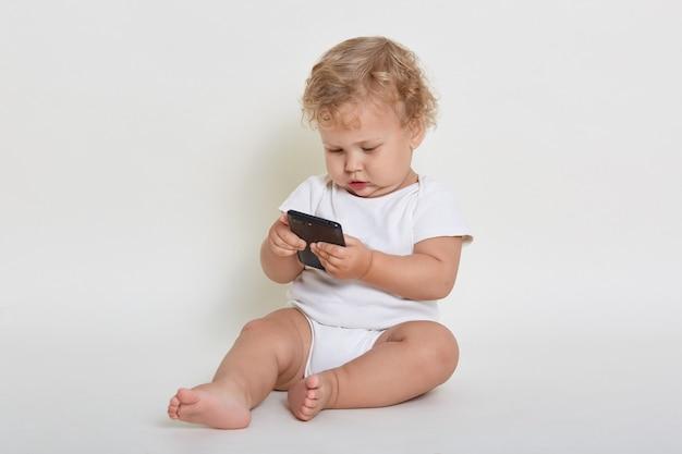 Nieuwsgierige babyjongen zittend op de vloer met telefoon in handen