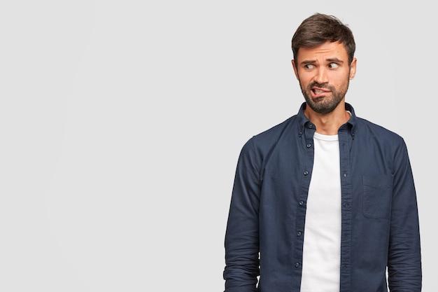 Nieuwsgierige bebaarde jonge europese man kijkt zenuwachtig, tuitjes lippen en staart wantrouwend opzij, gekleed in vrijetijdskleding, staat alleen tegen witte muur met copyspace