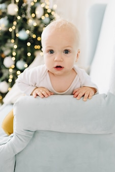 Nieuwsgierige blanke baby zittend in een fauteuil met kerstboom Premium Foto