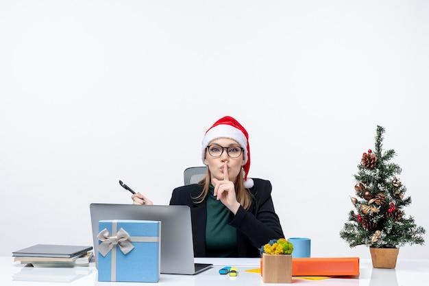 Nieuwsgierige blonde vrouw met een kerstman hoed zittend aan een tafel met een kerstboom en een cadeau erop op witte achtergrond