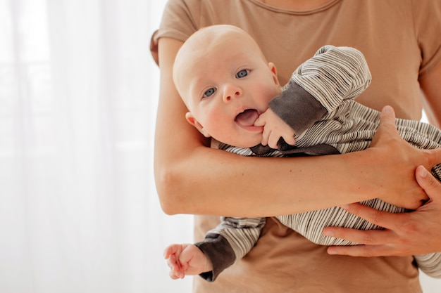 Nieuwsgierige brutale baby op handen van moeder