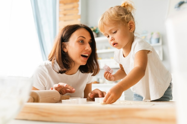 Nieuwsgierige dochter en gelukkige moeder die koekjes voorbereiden