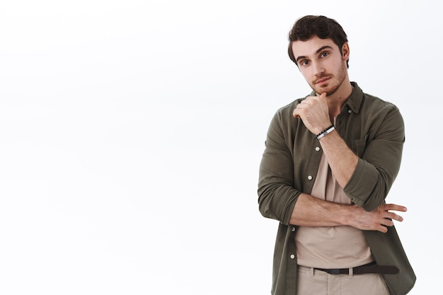 Nieuwsgierige en enthousiaste jonge blanke bebaarde man die in de buurt van lege witte kopieerruimte staat