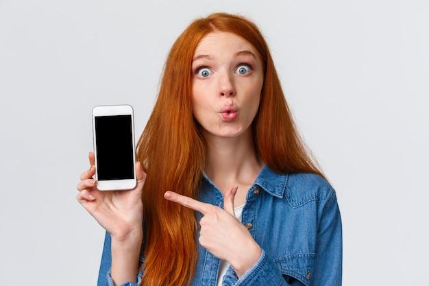 Nieuwsgierige en geamuseerde mooie roodharige vrouw met lang rood haar, vouwen lippen geïntrigeerd en opgewonden, discussiëren over nieuwe app, foto's van klasgenoot met nieuwe auto, wijzende vinger smartphone, roddelen
